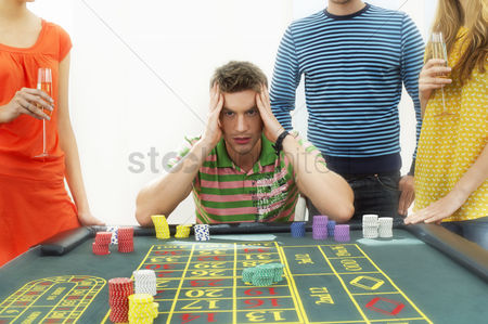 Loss : Young frustrated man at roulette table with friends