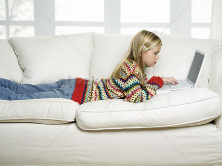 Children playing : Young girl lying on stomach on sofa using laptop side view