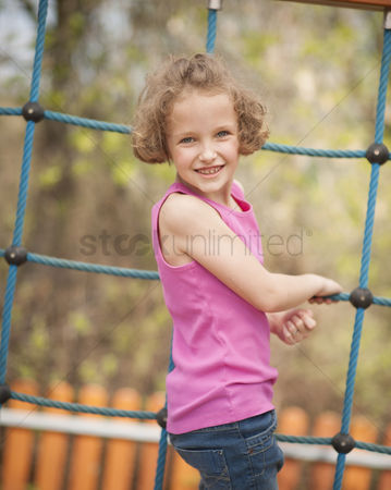 Excited : Young girl on climbing net turning to face camera