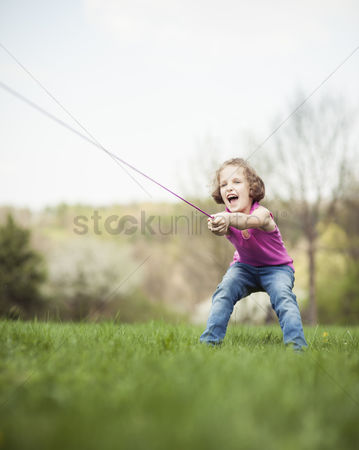 Excited : Young girl playing tug of war