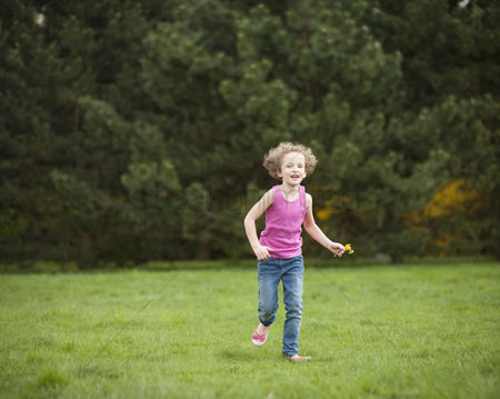 Excited : Young girl running through park in summer