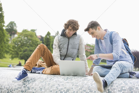 University : Young male college friends with laptop studying together in park