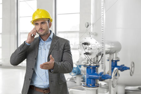 Supervisor : Young male engineer using cell phone in industry