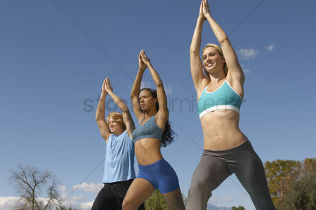 Fitness : Young man exercising with two young women in park