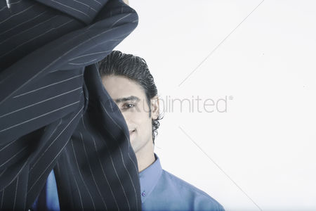 Man suit fashion : Young man holding a coat in front of his face