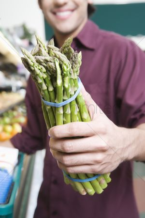 Selection : Young man holding asparagus in supermarket