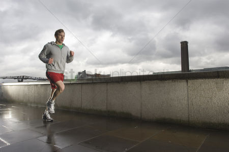 Fitness : Young man jogging besides the thames in london on stormy day