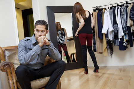 Selection : Young man sitting on armchair looking away while girlfriend looking herself in mirror