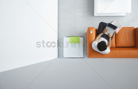 Furniture : Young man using laptop in reception room view from above