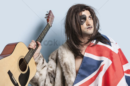 British ethnicity : Young man with british flag holding guitar against light blue background