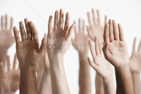 Young woman : Young men and women raising hands close-up of hands