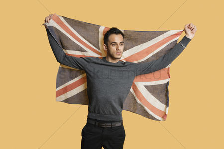 British ethnicity : Young patriotic man lifting british flag over colored background