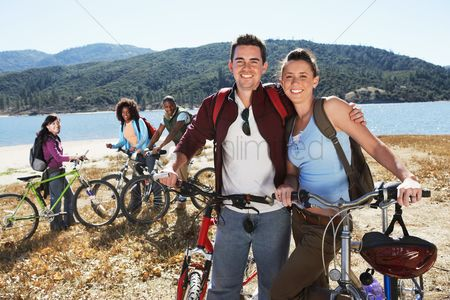 Relationships : Young people standing with mountain bikes in front of lake