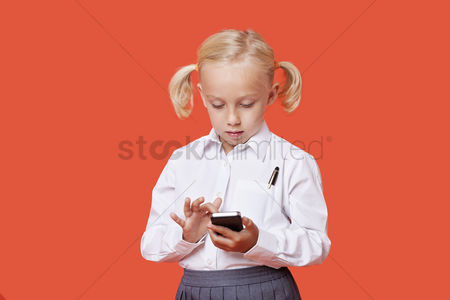Ponytail : Young school girl reading text messages over orange background