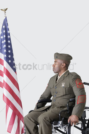 Respect : Young us soldier in wheelchair looking at american flag over gray background