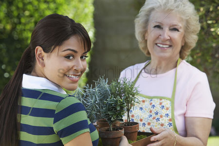 Offspring : Young woman and mother gardening portrait