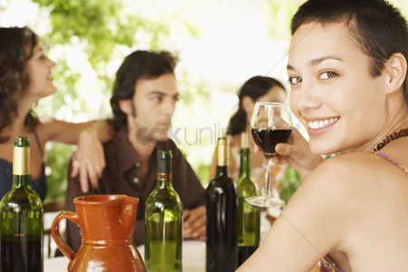Wine bottle : Young woman at table holding glass of red wine with small group of young people in background portrait
