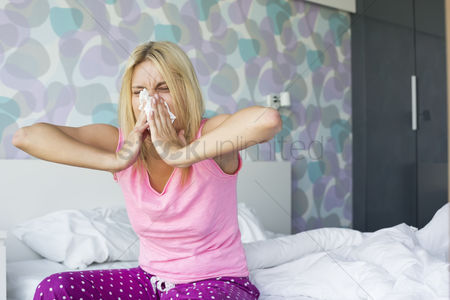 Blowing : Young woman blowing her nose in tissue paper while sitting on bed