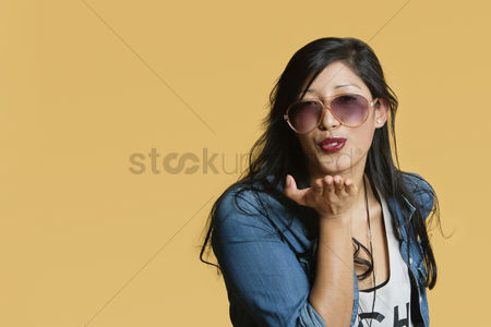 Head shot : Young woman blowing kisses over colored background