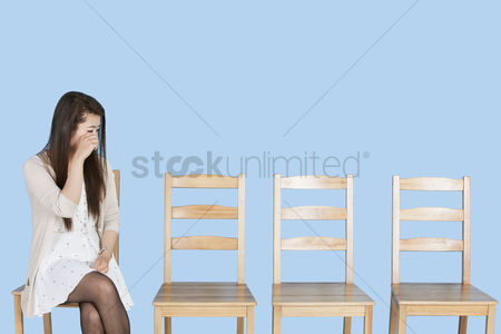 Worry : Young woman crying besides empty wooden chairs over blue background
