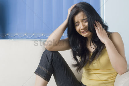 Pressure : Young woman crying on a couch with her head in her hand