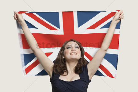 British ethnicity : Young woman holding british flag with pride over gray background
