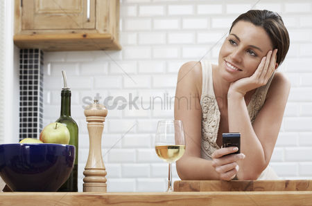 Wine bottle : Young woman holding mobile phone leaning on kitchen counter