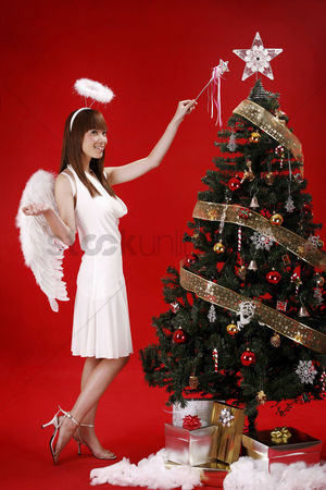 Religion : Young woman in angel costume standing beside christmas tree