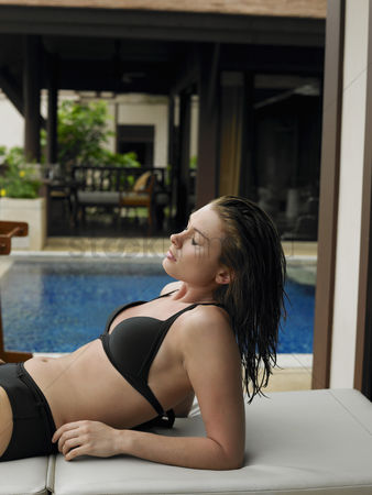 Comfy : Young woman in bikini by swimming pool