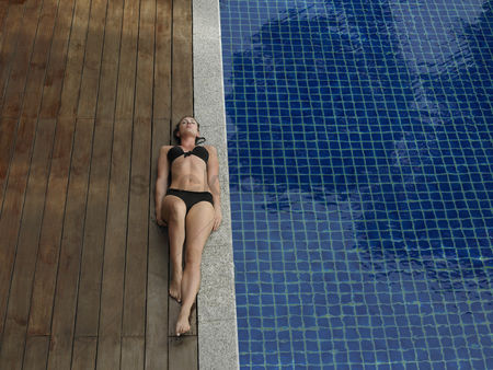 Comfy : Young woman in bikini lying by swimming pool