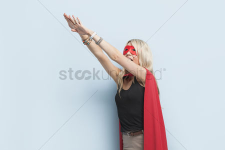 Blue background : Young woman in superhero outfit pretending to leap in the air against light blue background