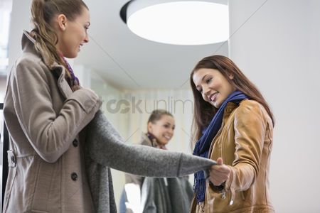 Jacket : Young woman looking at friend wearing jacket in clothing store