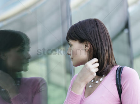 Fixing : Young woman looking at reflection of self in building window