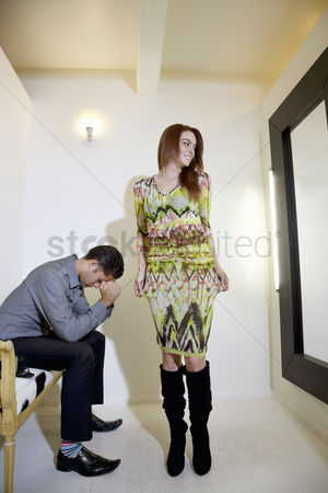 Spending money : Young woman looking at self in mirror while man sitting on chair with hands on face