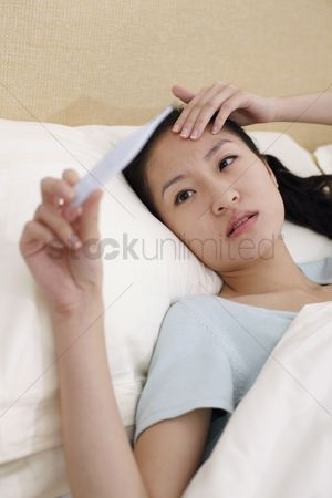 Thermometer : Young woman lying in bed holding thermometer