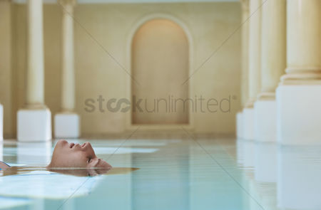 Contemplation : Young woman lying on back in swimming pool portrait