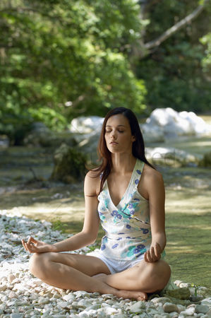 Contemplation : Young woman meditating by forest river full length