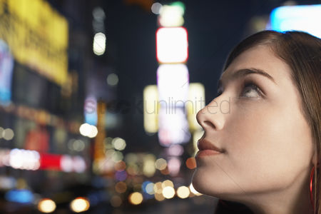 Pensive : Young woman on nighttimes city street close up profile