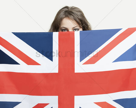 British ethnicity : Young woman peeking over british flag against gray background