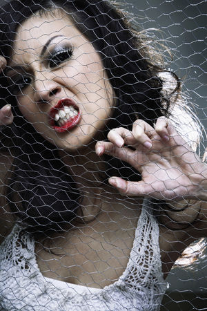Rage : Young woman posing behind wire mesh