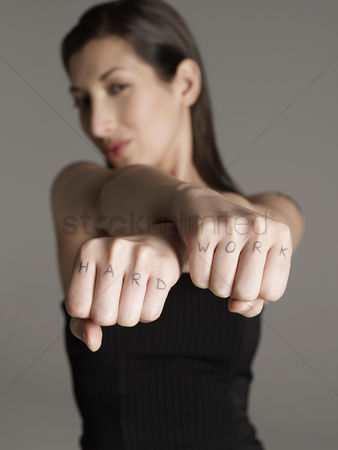 Arm raised : Young woman showing fists with  hard work text focus on foreground