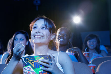 Girls : Young woman sitting in theatre eating popcorn watching movie