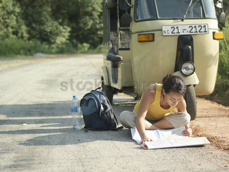 Asian : Young woman sitting on road reading map motor scooter in background
