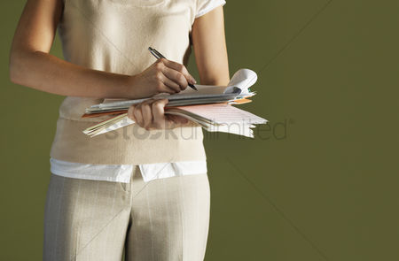Notepad : Young woman standing holding notepad writing mid section