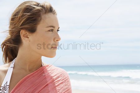 Summer : Young woman standing on beach close-up head and shoulders