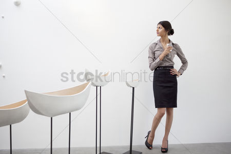 Interior background : Young woman standing with glazed ceramics boats