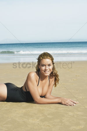 Gaze : Young woman sunbathing on beach