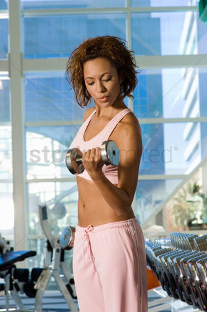 Dumbbell : Young woman using dumbbell in gymnasium