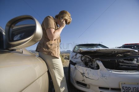 Transportation : Young woman using mobile phone by car wreckage