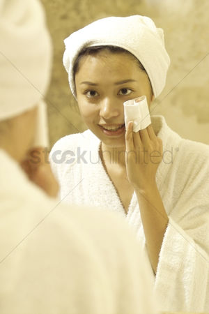 Interior : Young woman wiping face in the mirror
